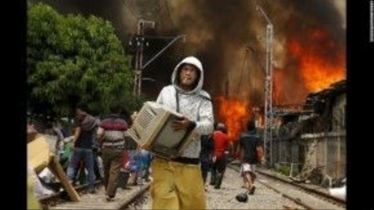 26/1: Một đám cháy lớn ở thủ đô Jakarta, Indonesia đã thiêu rụi hơn 100 căn nhà dọc một đường ray xe lửa. Trong ảnh, một người đàn ông đang sơ tán một chiếc Tivi ra khỏi hiện trường.