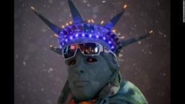23/1: Một người đàn ông hóa trang thành bức tượng Nữ thần Tự do giữa lúc thành phố New York tuyết trắng trời vì bão.