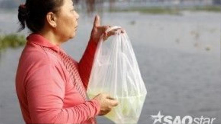 Một người dân gửi gắm mong ước những điều tốt đẹp sẽ đến với bản thân và gia đình trong năm mới vào chú cá mà cô sắp thả.