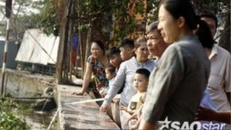 Những vị khách viếng chùa cũng hiếu kỳ, ra bờ sông xem người ta thả cá.