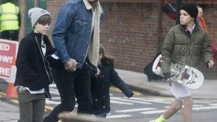 4 bố con vội vã băng qua đường. Cựu danh thủ Anh mặc đồ trẻ trung, cẩn thận dắt hai con nhỏ sang đường.
