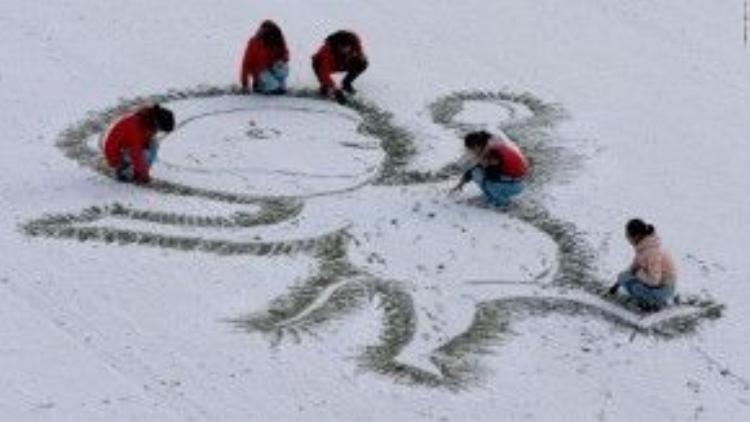 Giáo viên và học sinh cùng vẽ hình khỉ trên tuyết ở tỉnh Giang Tô, Trung Quốc.