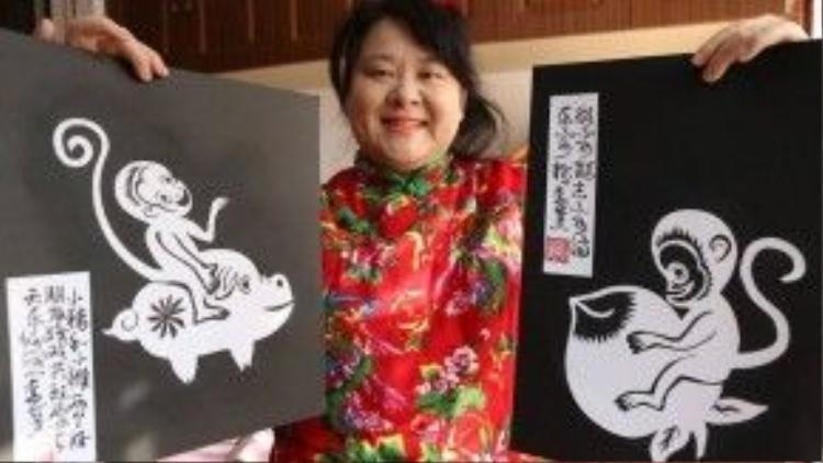 Dù thị lực của cả hai mắt đều rất kém, thế nhưng nghệ nhân cắt giấy Li Dai ở Thượng Hải, Trung Quốc vẫn miệt mài làm việc và cho ra đời nhiều sản phẩm cắt giấy đạt nhiều giải thưởng trong và ngoài nước. Trong ảnh, cô trông rất sẵn sàng chào đón năm mới với bộ đồ đỏ và hai bức tranh khỉ do chính tay mình làm ra.