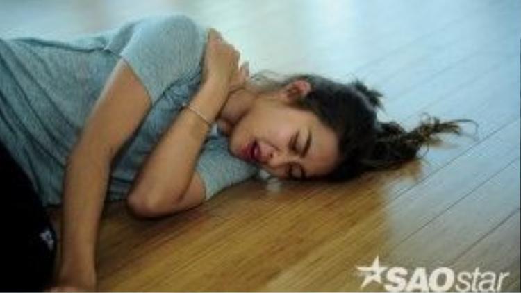 Trên sàn tập, Khả Ngân nằm bệt xuống sàn khi bị đau ở vai do cố sức tập những động tác mới đòi hỏi sự dẻo dai và chuyên nghiệp.