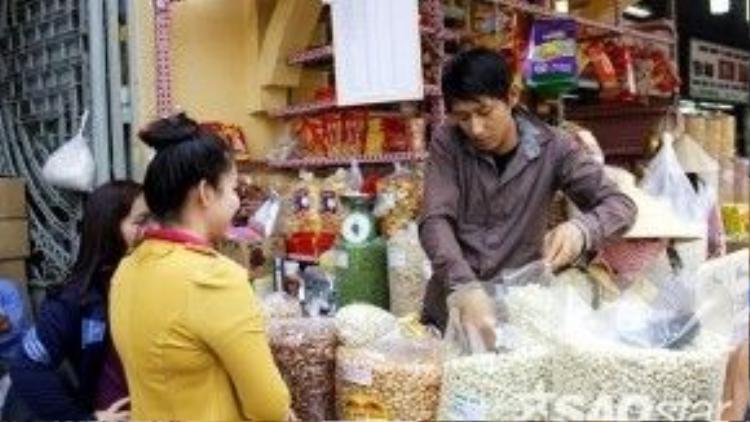 Cácquầy hàng nằm ở mặt ngoài chợ còn có khách ra khách vào thường xuyên.