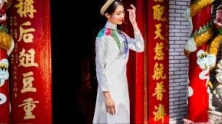 Cô nàng trông thật tinh khôi với áo dài trắng, phần cổ áo được phối nhiều màu sắc giúp chiếc áo thêm phần lộng lẫy.