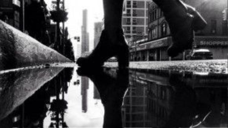 Đôi chân của một người phụ nữ trẻ in rất rõ trên bóng nước.