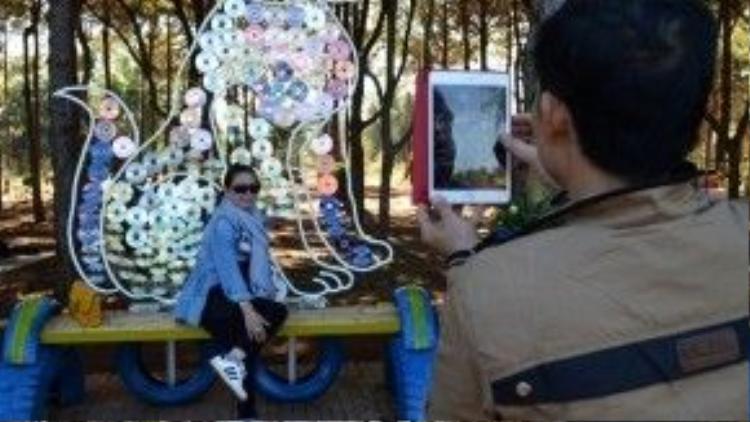 Du khách thích thú chụp hình với chú chó được làm thừ những thanh thép và đĩa CD bỏ đi.