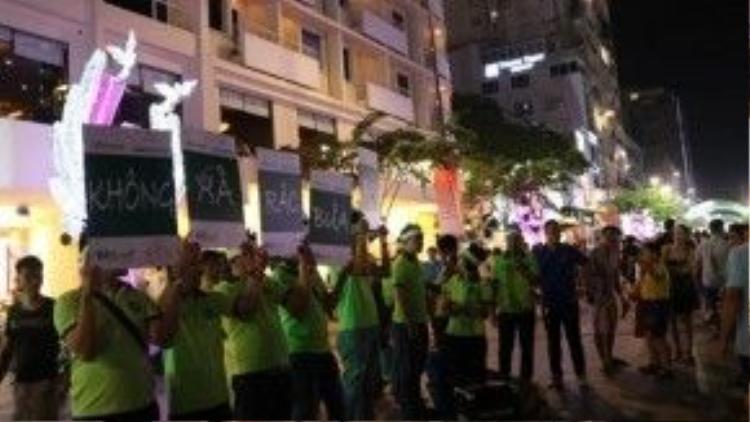 """Các bạn đoàn viên thanh niên quận 1 cầm bảng kêu gọi người tham quan đường hoa Nguyễn Huệ """"Không xả rác bừa bãi"""" ngay trong đêm giao thừa."""