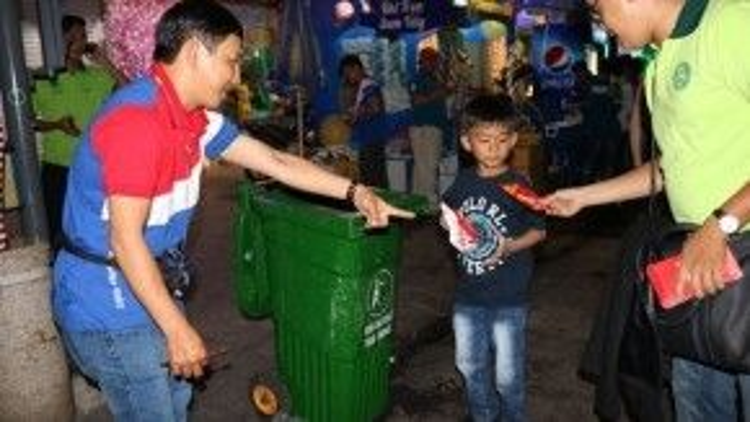 Một bạn nhỏ bỏ rác vô thùng nhận được lì xì.