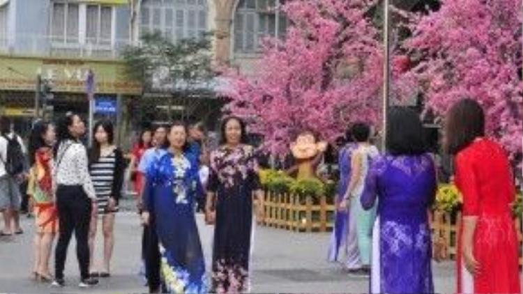Áo dài là một trong những trang phục được đa phần phái đẹp lựa chọn cho buổi vãn cảnh xuân tại đường hoa Nguyễn Huệ. Ảnh: Vũ Nguyễn.