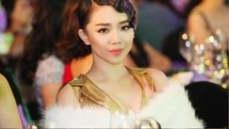 Tiên chọn cho mình chiếc váy metalic ánh vàng đi dự sự kiện kèm áo khoác trắng và đôi môi màu đào ngọt ngào.