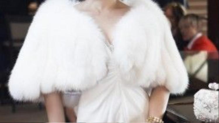 Cô lần nữa lại ghi điểm với chiếc áo khoác lông kiêu kỳ kết hợp cùng váy trắng dáng ôm dài và vòng tay ngọc trai sang trọng.