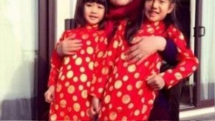 Hai con Chung Lệ Đề mặc áo dài tạo dáng bên bà ngoại.