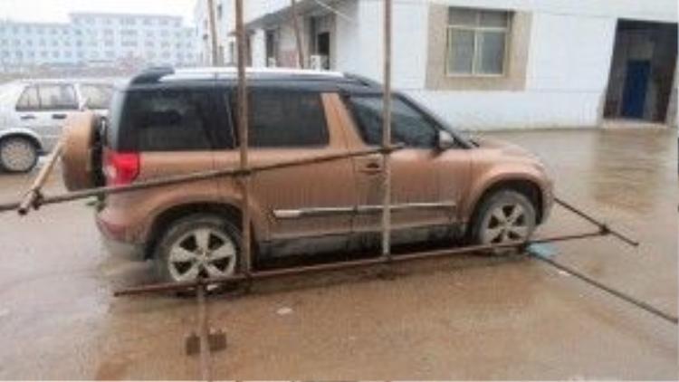 Ngày 27/1, chiếc xe mang biển số của tỉnh Giang Tô này đã bị những người công nhân dùng 12 thanh sắt khóa chặt trong công ty.