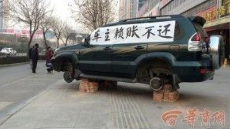 """Ngày 28/1, người dân ở Lâm Vị, Vị Nam, Thiểm Tây đã vô cùng ngạc nhiên khi nhìn thấy một chiếc xe việt dã bị gỡ mất 3 bánh xe đỗ bên lề đường, trên thân xe còn dán tờ giấy rất to ghi dòng chữ: """"Chủ xe chầy bửa không chịu trả nợ""""."""