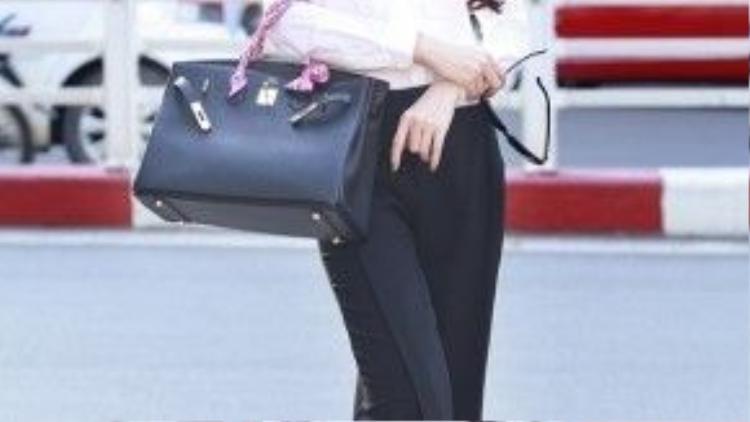 Chiếc túi trông có hơi quá khổ so với set trang phục và để tinh tế hơn, cô nên thay một chiếc váy dài xếp li đen, vừa hợp mốt vừa nữ tính.