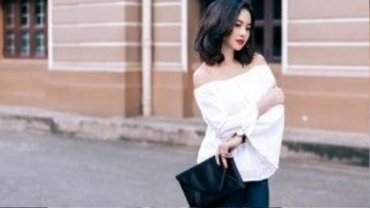 Điệu đà với áo trễ vai trắng cùng túi hình bì thư đen.