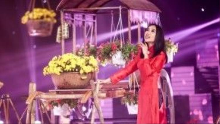 """Sự kết hợp tinh tế giữa áo dài đỏ cùng quần bó màu đen - trang phục """"kinh điển"""" của """"Chocolate"""" trong nhiều năm qua - giúp Đoan Trang trông có vẻ đằm thắm, dịu dàng hơn. Theo Đoan Trang, trước đây khi chưa lập gia đình, cô là người rất """"năng nổ"""" với các show diễn dịp Tết."""