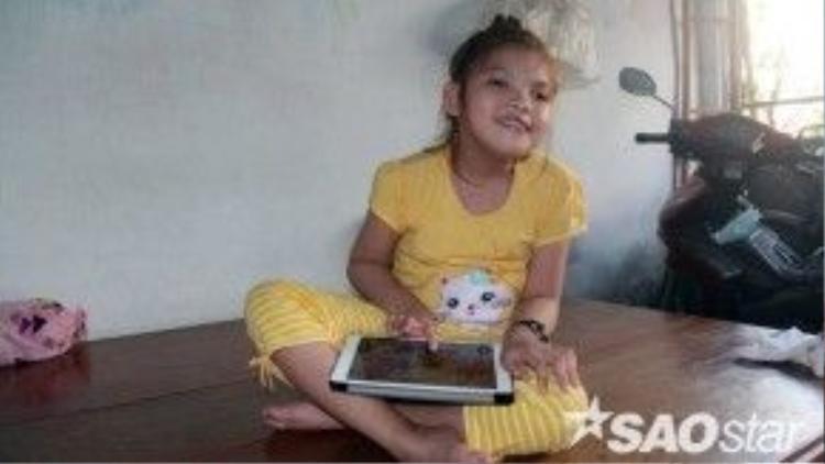 Sau thời gian điều trị, bé Thanh Tuyền có thể ngồi được và cự động nhẹ đôi tay trên chiếc máy tính bảng mà một nhà hảo tâm trao tặng.