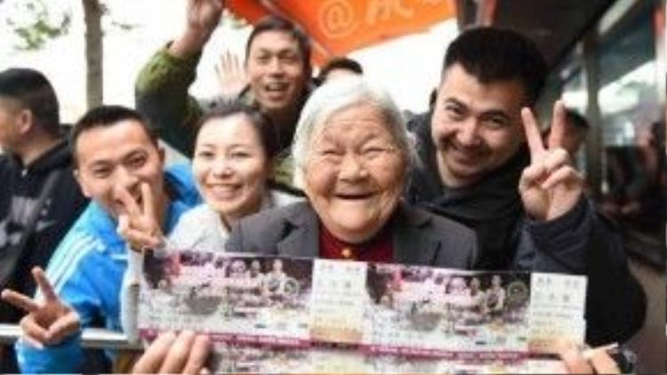 Nụ cười mãn nguyện của cụ Meng khi cầm trên tay tấm vé mua được chocon trai. Những người xung quanhcũng vui lây cùng cụ.