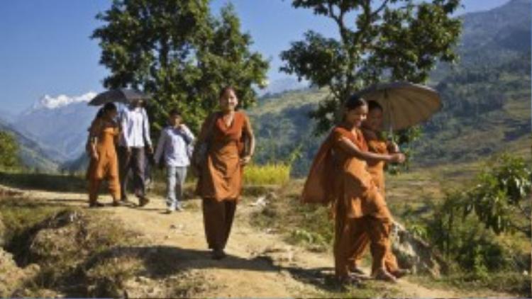 Các nữ sinh Nepal trong đồng phục màu cam đang đi qua những ngọn đồi cao để tới trường ở Manaslu.