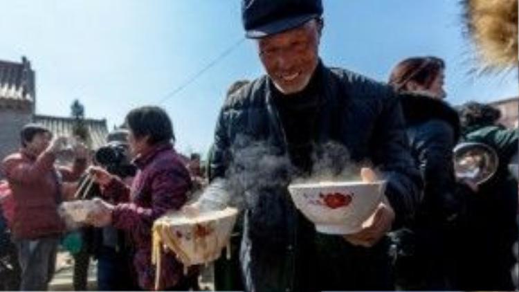 Một người đàn ông hí hửng vì lấy được những 2 bát mì. Ảnh: Shanghaiist