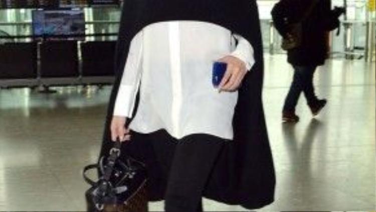 Và kết thúc ngày tại sân bay Heathrow, mặc quần skinny jean, một chiếc áo sheer và áo khoác choàng cách điệu nửa người vạt trước.