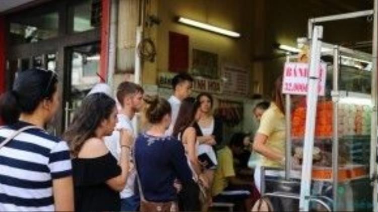"""Do nằm ở vị trí trung tâm, người dân Sài Gòn lẫn du khách nước ngoài thườngtìm đến và kiên nhẫn xếp hàng để được cầm trên tay và thưởng thức""""chiếc bánh mì đắt nhất Sài Gòn""""."""