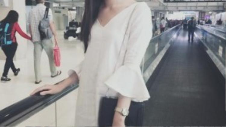 Xuất hiện ở cảng hàng không quốc tế Thái Lan, Phạm Ngọc Quý chọn cho mình một chiếc váy trắng dáng suông cổ chữ V, tay áo loe. Chuyến bay kéo dài hơn 1 tiếng nên chiếc váy rộng rãi sẽ giúp chân dài thoải mái hơn khi ngồi trên máy bay.