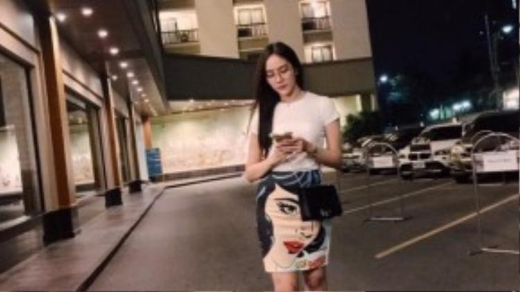 """Ngày đầu tiên ở Thái, cô mặc set đồ đơn giản bao gồm chân váy ôm họa tiết khuôn mặt và áo thun trắng. Cô từng chia sẻ trên trang cá nhân khi cô là một tín đồ """"cuồng"""" màu trắng."""