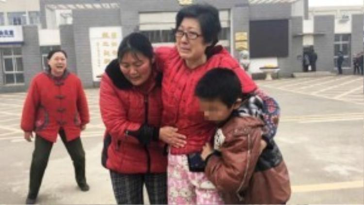 """Vào ngày """"mẹ hổ"""" Li Zhengqin (đeo kính) được tại ngoại,một cảnh tượng không ai ngờ đến đã xảy ra bên ngoài nhà tùthành phố Nam Kinh (Trung Quốc) - nơi cô bị giam giữ trong 6 tháng trước đó. Những người có mặt để chào đón cô trở vềkhông ai khác chính là cậu bé nạn nhân của vụ bạo hành và mẹ ruột của em."""