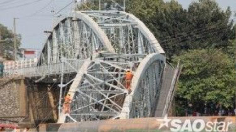 Lực lượng chức năng phải đu dây tiếp cận hiện trường nơi chiếc sà lan lật úp cũng như xử lý sự cố điện tại nhịp 2 cầu Ghềnh. Chính quyền TP Biên Hòa cho biết đang lên phương án xây dựng cầu tạm qua sông.