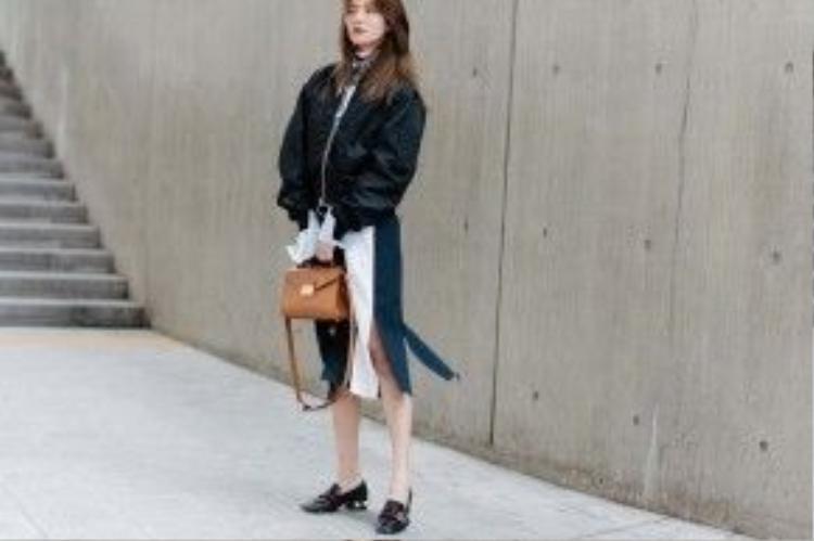 Bomber đen khỏe khoắn kết hợp cùng chân váy tạo nên sự đối lập nhưng lại vô cùng hòa hợp. Đôi giày theo phong cáchmenswear Gucci chính là điểm nhấn phá cách cho tổng thể set đồ.