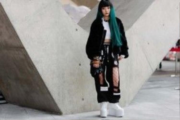 Một cô bạn cá tính với style gothic với màu tóc nhuộm nổi bật, quần thụng với tất lưới mặc bên trong và đôi giày đế độn hàng khủng.