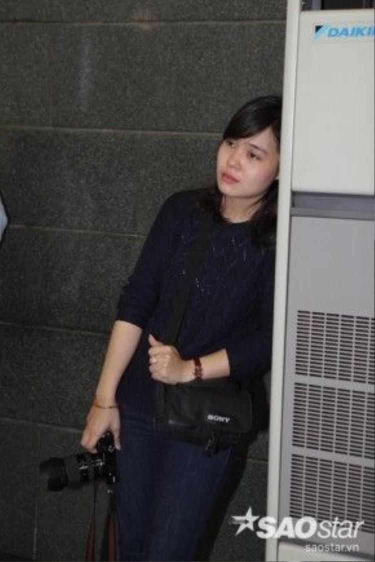 Một phóng viên nữ tay cầm máy ảnh, đứng dựa tường khóc thương cho vị nhạc sĩ tài hoa nhưng bạc mệnh.