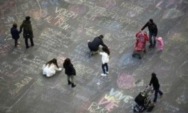 Người dân và du khách đang viết thông điệp trên mặt đường quảng trường Bourse, trước Trung tâm Chứng khoán Brussels. Ảnh: Kenzo Tribouillard/AFP/Getty Images
