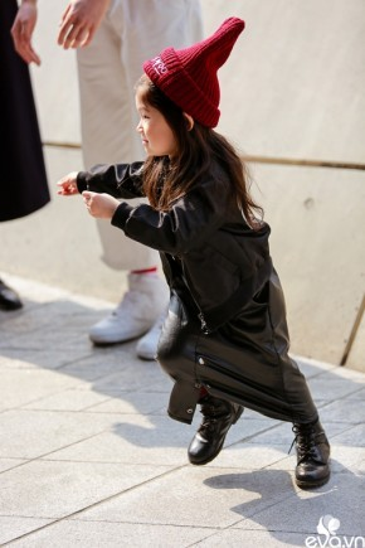 Một màu đen làm chủ đạo cho cả bộ đồ. Em bé diện chân váy da cùng mũ hoodie đáng yêu.