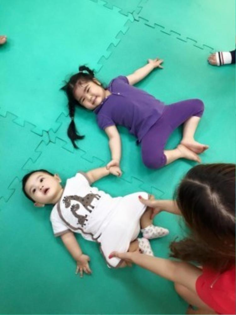 Kubi diện bộ thun trắng họa tiết thú ngộ nghĩnh theo mẹ đến phòng tập. Trang phục co giãn giúp bé thoải mái vui chơi.
