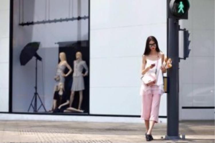 Người mẫu Nguyễn Thùy Dương xuống phố với dáng vẻ luộm-thuộm-một-cách-có-đầu-tư. Chiếc áo ngủ dây mảnh pha voan diện cùng quần culottes gam hồng thạch anh ngọt ngào rất được lòng của phái đẹp Sài thành hiện nay.