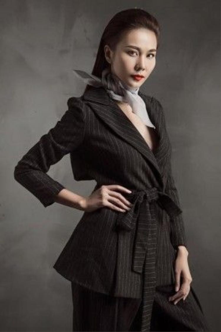 """""""Đệ nhất chân dài""""Thanh Hằng cũng là một trong những fashionista đam mê với kiểu thắt khăn cổ điển này. Với bộ suit đen mang đậm phong cách menswear cá tính, cô nàng đã phối hợp nhuần nhuyễn với món phụ kiện là chiếc khăn lụa thắt quanh cổ giúp cân bằng lại nét nữ tính vốn có của chủ nhân."""