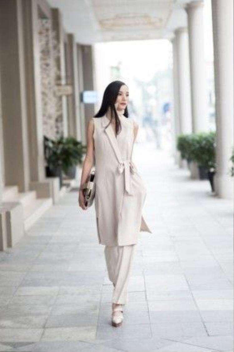 Người mẫu Lê Thúy lại xuống phố với phong cách theo trường phái minimalist (đơn giản vẫn là nhất) trong bộ vest cách điệu dáng dài cùng quần ống suông ton-sur-ton. Để làm tăng phần thu hút, cô nàng cũng đã dùng món phụ kiện khăn lụa mỏng thắt quanh cổ tạo điểm nhấn cho set đồ.