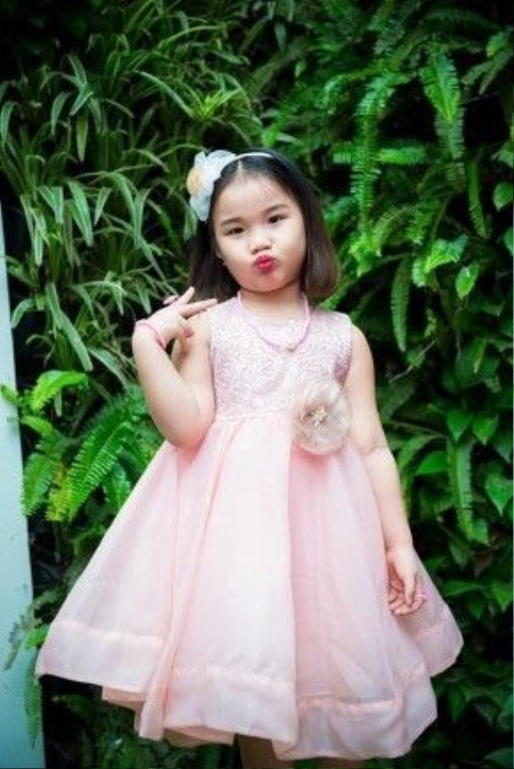 Trong bộ váy màu hồng như nàng công chúa, bé Vi An tự tin tạo dáng trước ống kính máy ảnh mà không cần có mẹ ở bên.