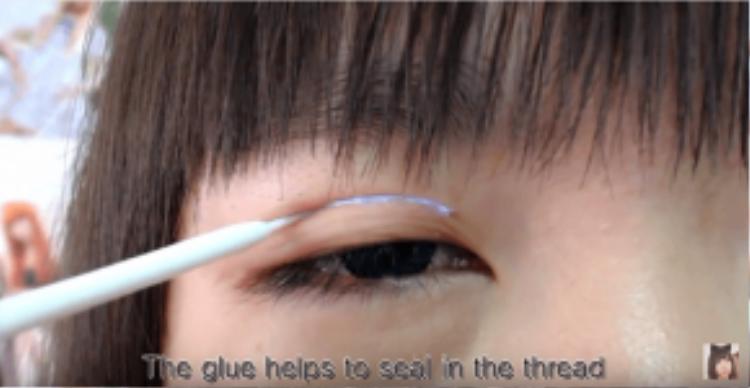 Để định hình chắc đường chỉ, bôi 1 lớp gel/keo kích mí.Sau đó dùng cây phụ kiện nâng mí lên
