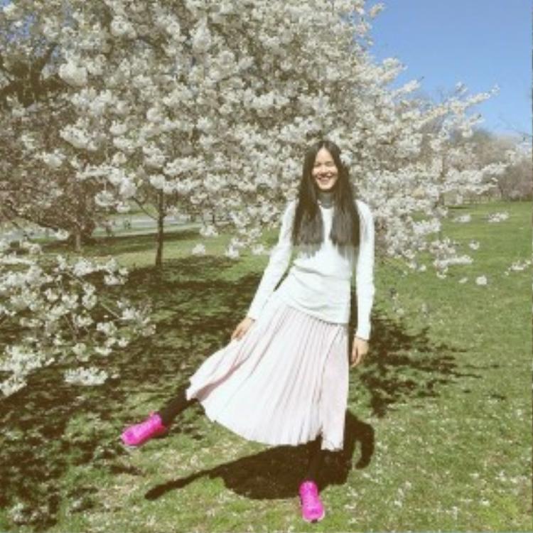 Tuyết Lan khoe streetstyle độc đáo với váy xếp li màu hồng phấn cùng áo cashmere cổ lọ. Điểm nhấn của bộ trang phục là đôi giày sneaker năng động, trái ngược với diện mạo cực dịu dàng của siêu mẫu.