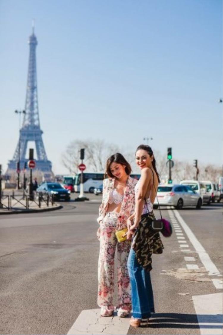 """Hai blogger thời trang đình đám của ThytguandMiu khoe ảnh streetstyle cực hút mắt trên đường phố Paris hoa lệ. Cô nàng miu diện pant-suit in hoạ tiết hoa cùng lace bralette trắng. Trong khi đó, cô nàng Thythu lại vô cùng cá tính với quần jean ống loe, áo khoác hoạ tiết camo khoác hờ ở eo. Thythu cũng không quên tăng sự quyến rũ bằng một đôi cao gót màu nude """"đế đỏ"""" cùng màu son cherry rực rỡ."""
