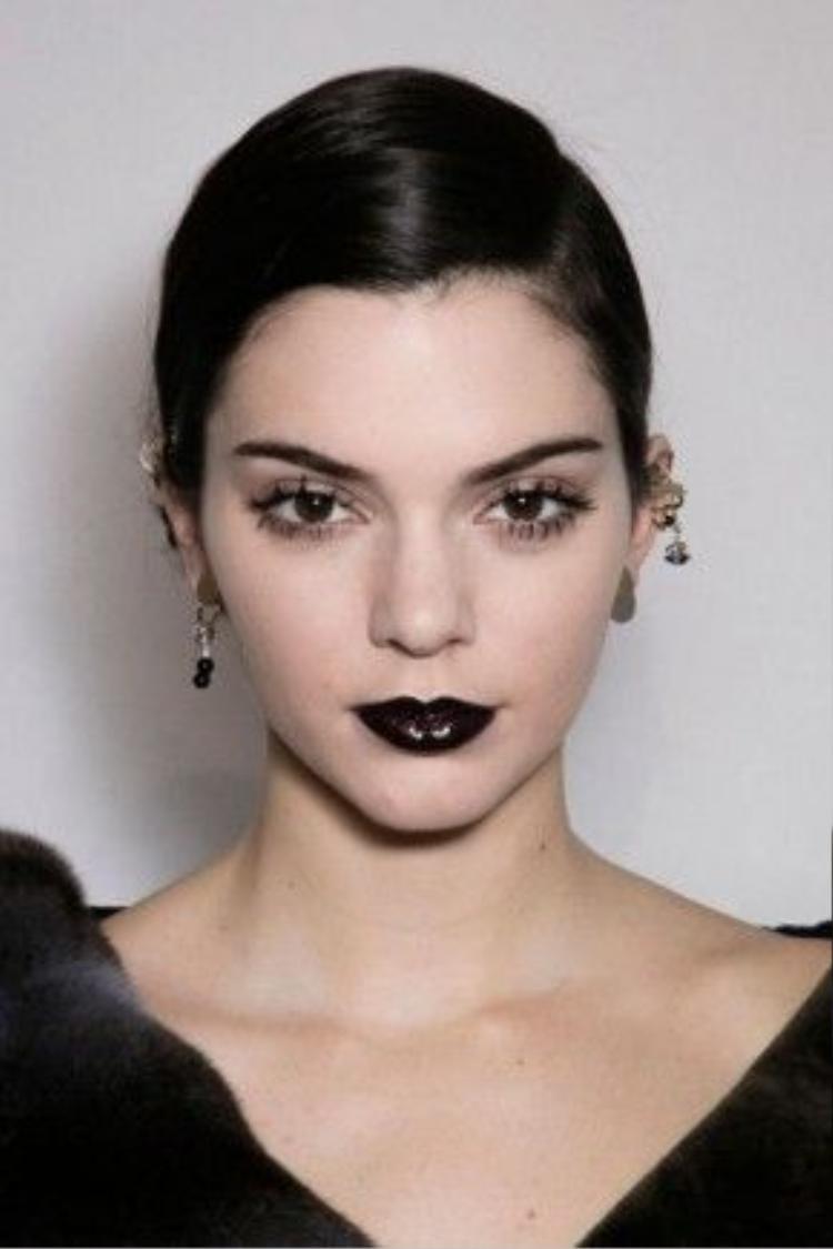 Son môi bóng với cố tình kẻ chuốt mascara vón cục đã tạo ra diện mạo khuôn mặt sắc lạnh của mẫu.
