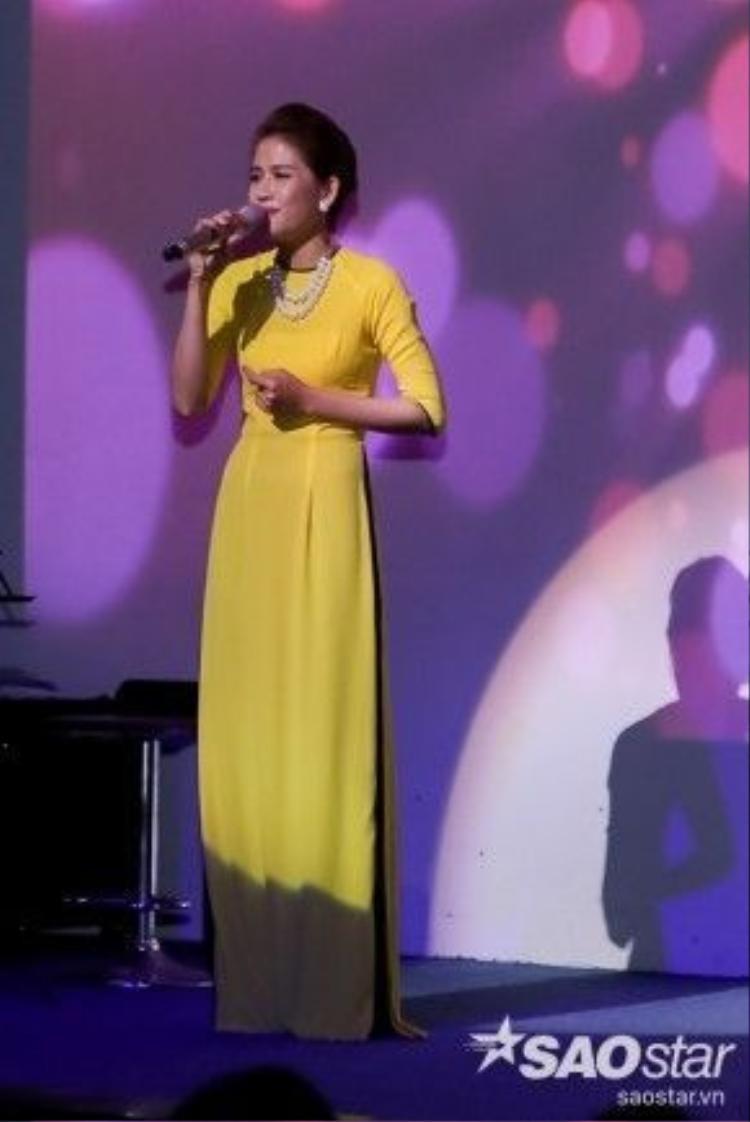 Lê Chinh dịu dàng trong tà áo dài trên sân khấu.
