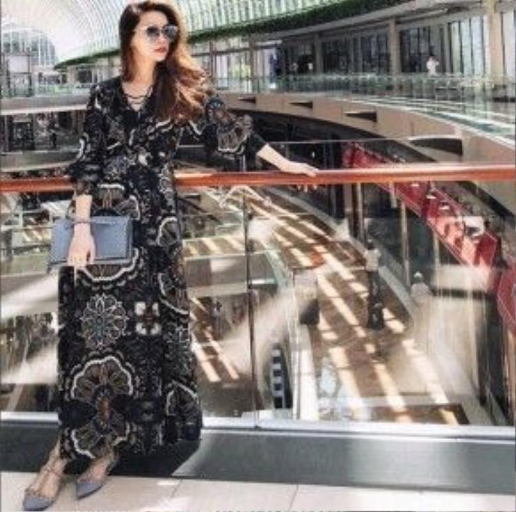 Hà Hồ diện một chiếc váy maxi mang theo phong cách cổ điển đậm nét thập niên 70s. Cô nàng chọn cách mix-match cùng những món phụ kiện xinh xắn như túi và giày của Valentino, kính mát của hãng SPRING STRINGS đến từ Hàn Quốc.