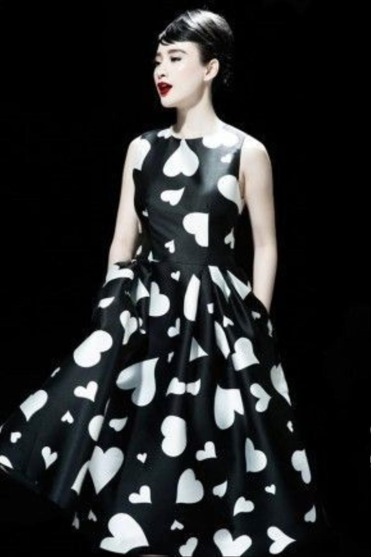 Bộ váy trắng xòe điểm xuyết họa tiết tim đen đã giúp Angela Phương Trinh trở thành tâm điểm trên thảm đỏ khai mạc Vietnam International Fashion Week 2015.